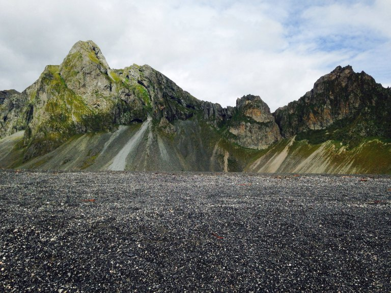 Black sand beaches and green mountains of scree and slag.
